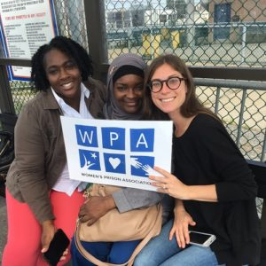 Three women holding the WPA logo